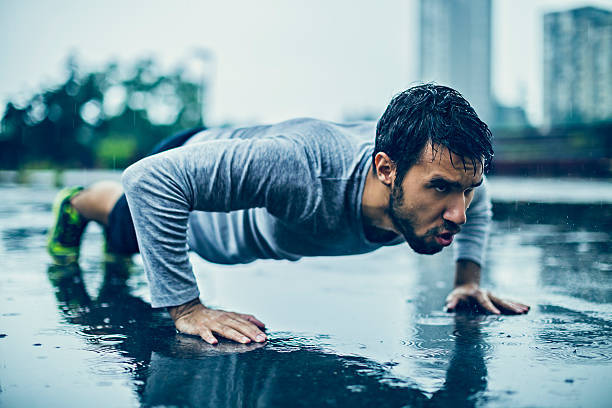 Man doing push-ups in the rain as part of his bodyweight chest workout