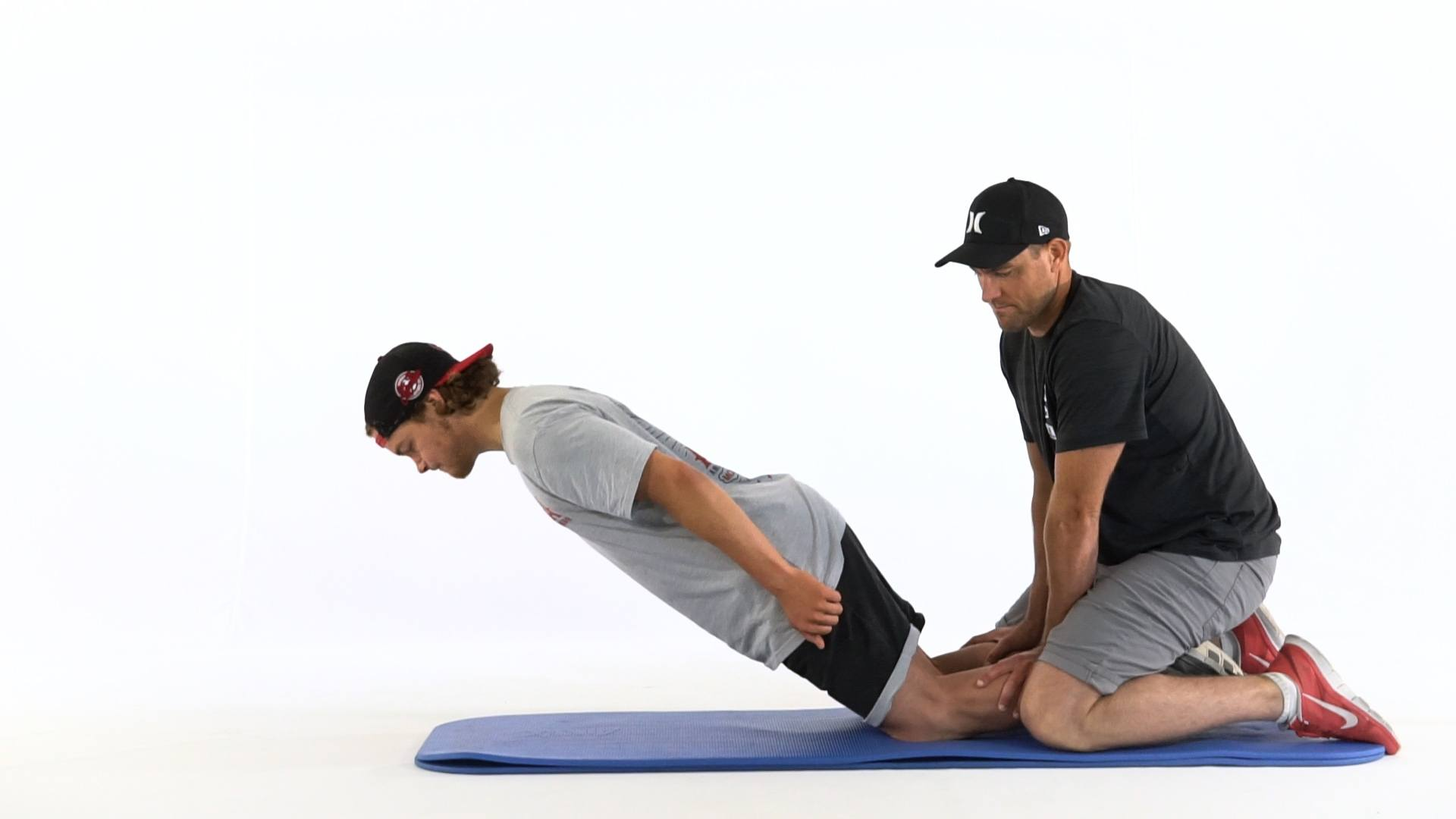 Picture of a man training natural leg curls while his workout partner is holding his legs in place