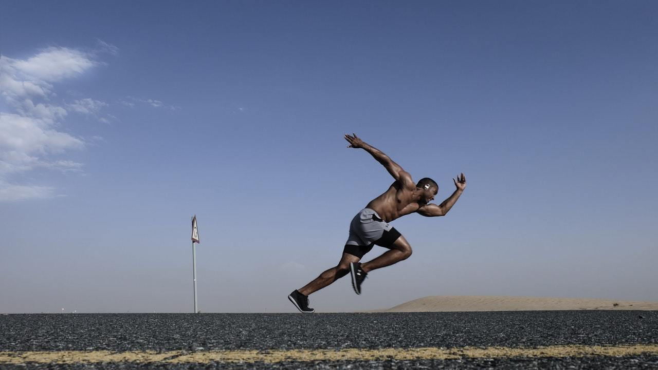 Man sprinting on a highway in the desert