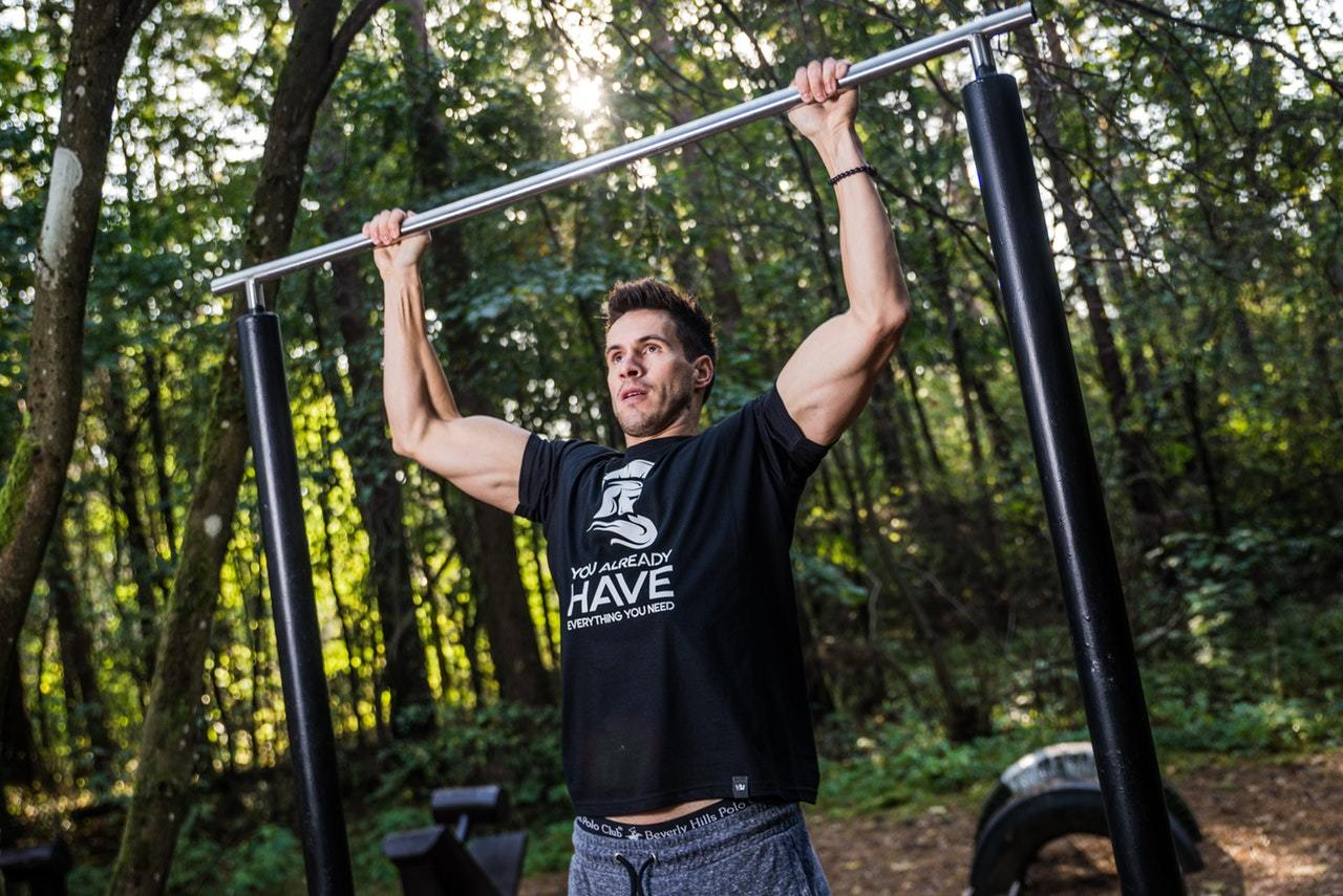 Photo of a man performing a pull-up on a bar in the woods