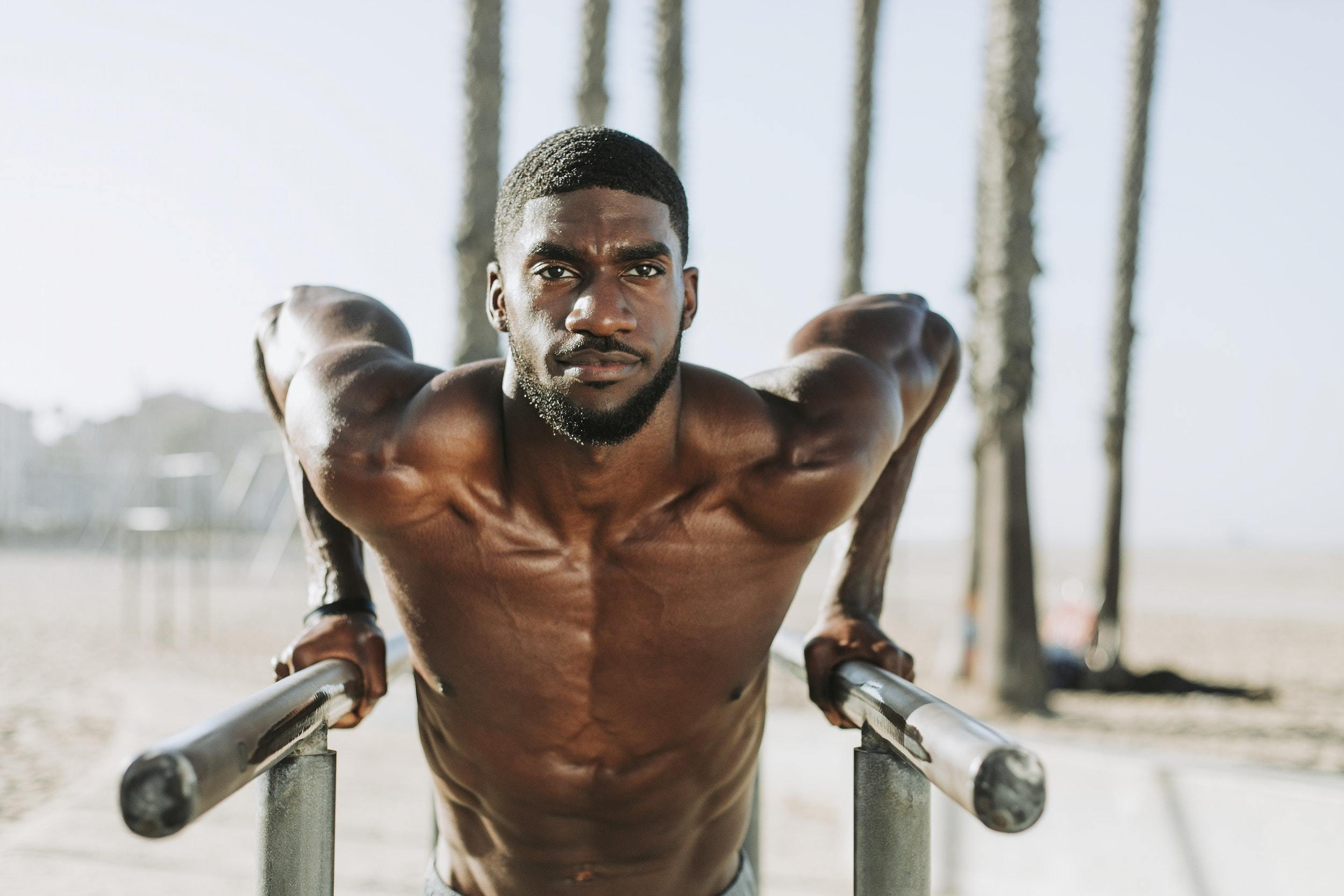 Man on the beach showing off his upper body muscles while doing dips