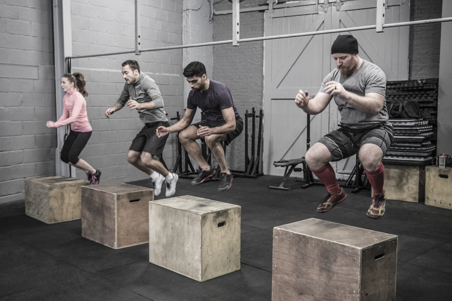 Four workout partners doing one of the best bodyweight leg exercises - the box jump
