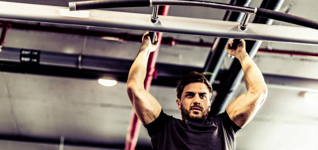 Athlete doing commando pull-ups, one of the best bodyweight bicep exercises