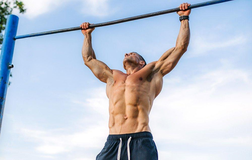Shirtless man doing a pull-up