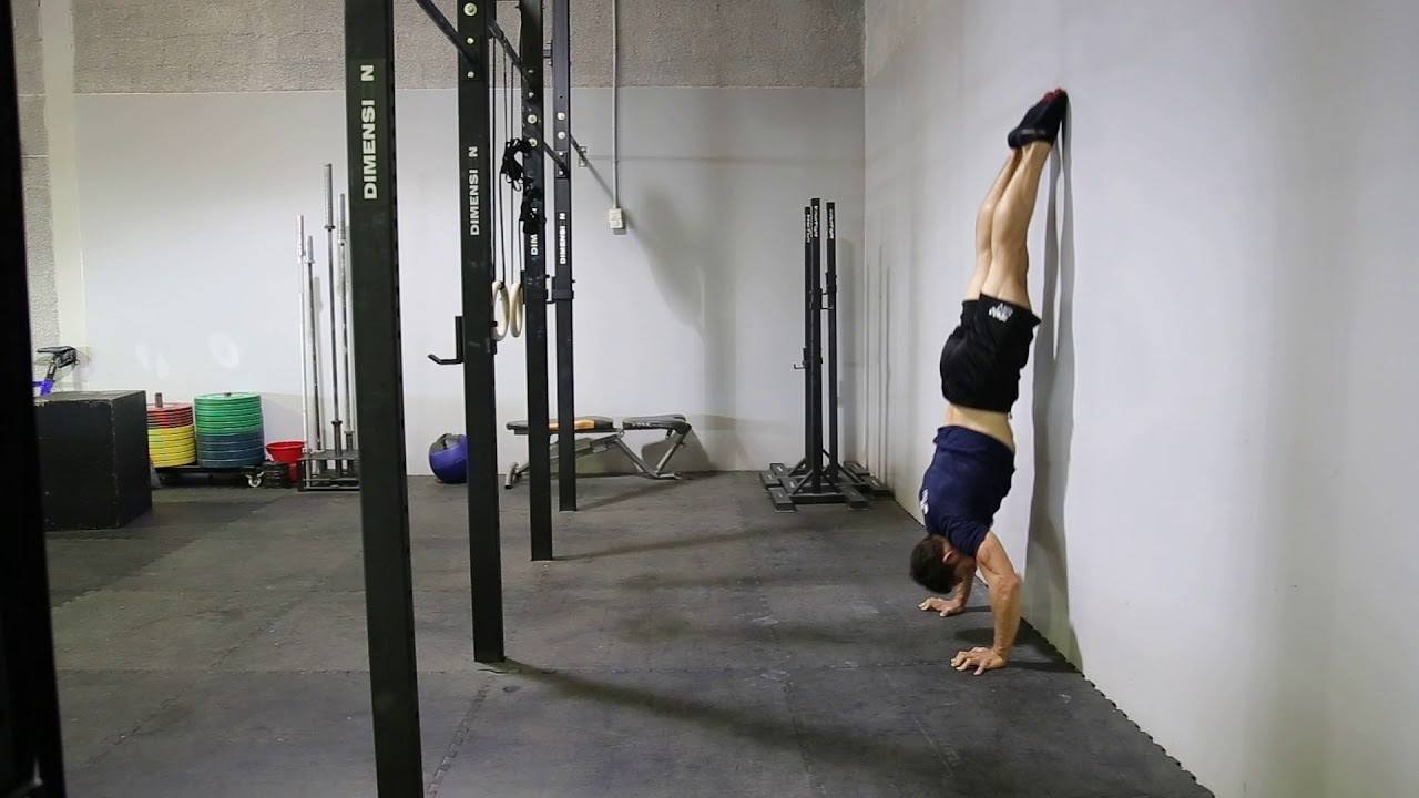 Athlete at a hymnastics' gym performing wall assisted handstand push ups