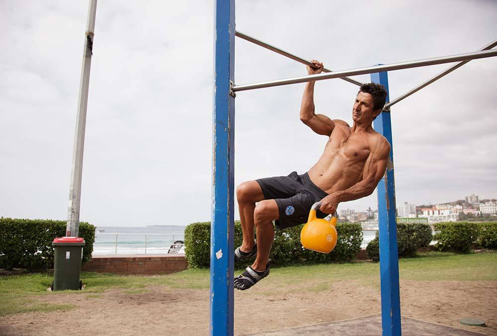 Marcus Bondi performing weighted one arm pull ups as par of his bodyweight back workout