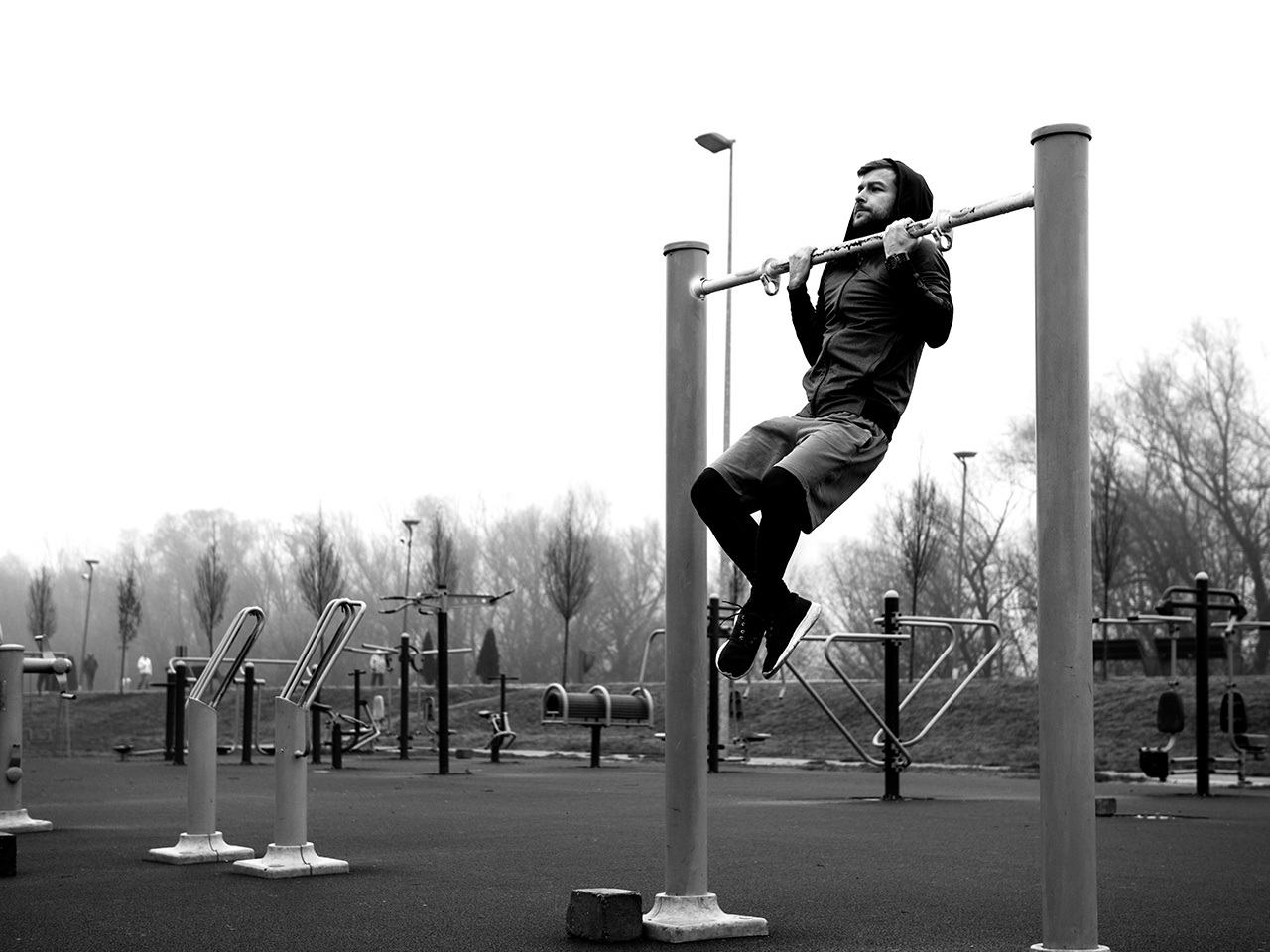 Man doing chin-ups in a park designed for workouts