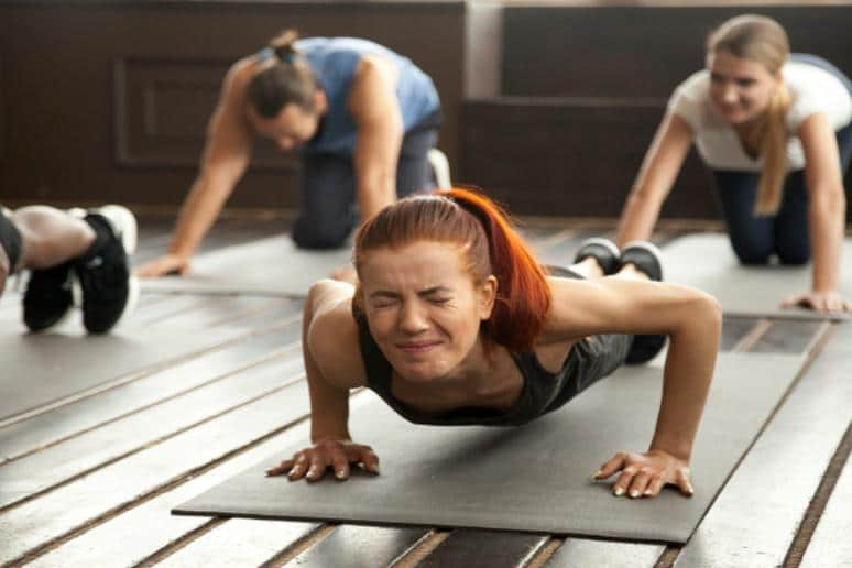 woman struggling to complete a repetition of a push-up