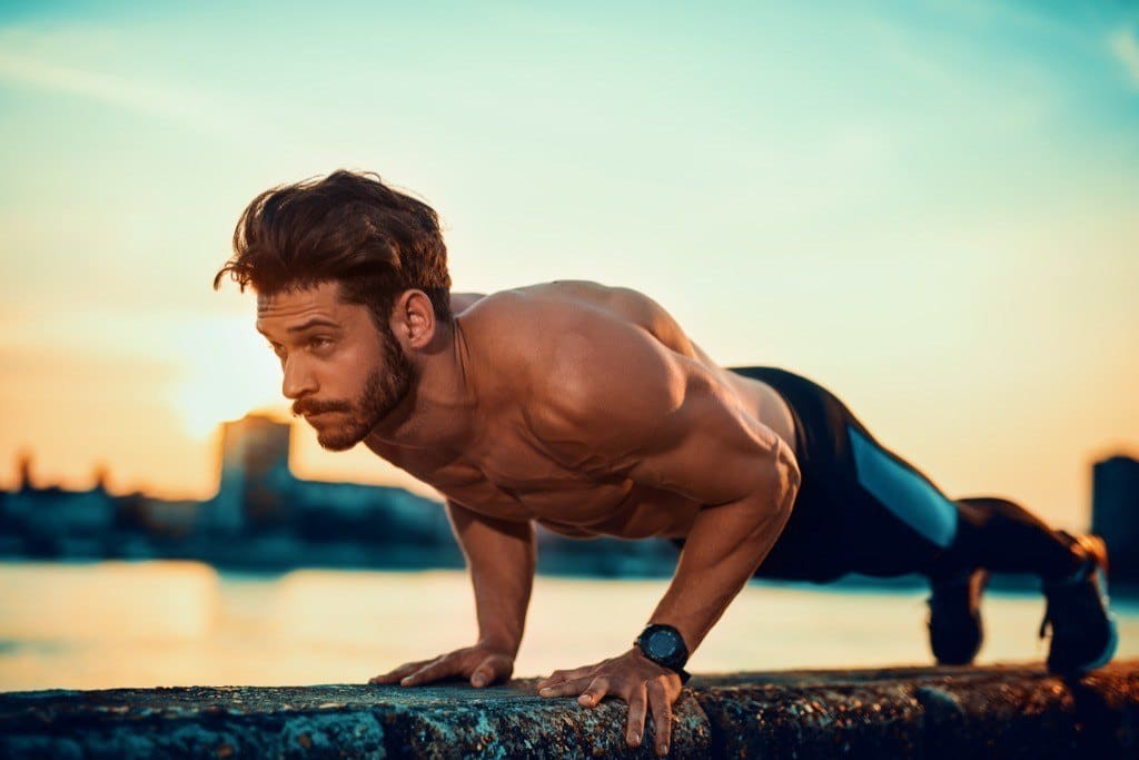 Man performing close grip push-ups on a ledge near a lake