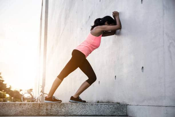 Woman stretching close to a wall