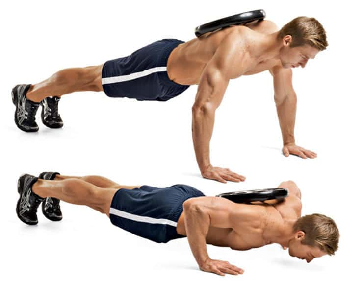 Man performing weighted push-ups with a weight plate on his back