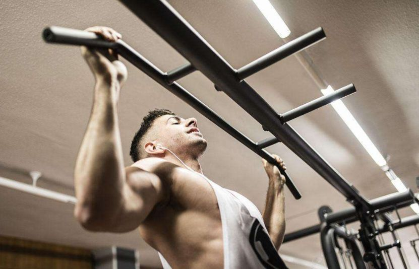 Athlete doing wide grip pull-ups, a bodyweight back exercise