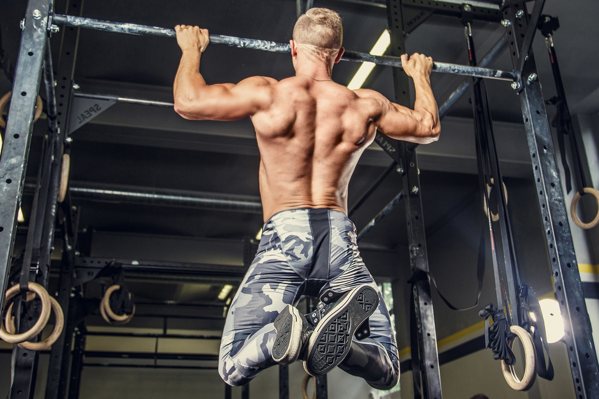 Athlete doing wide grip pull-ups