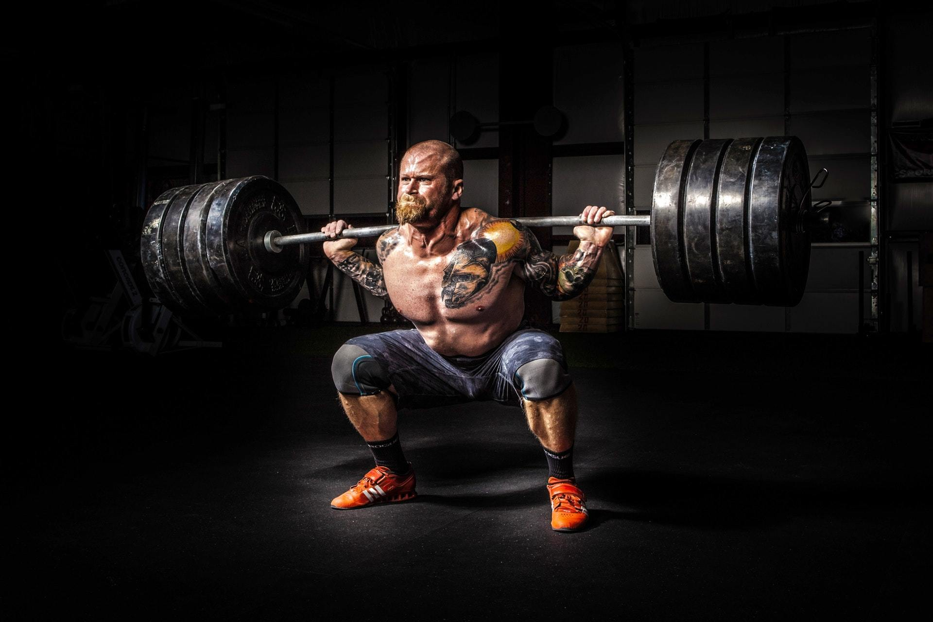 Man doing a squat using a heavy barbell using the best workout shoes for weightlifting