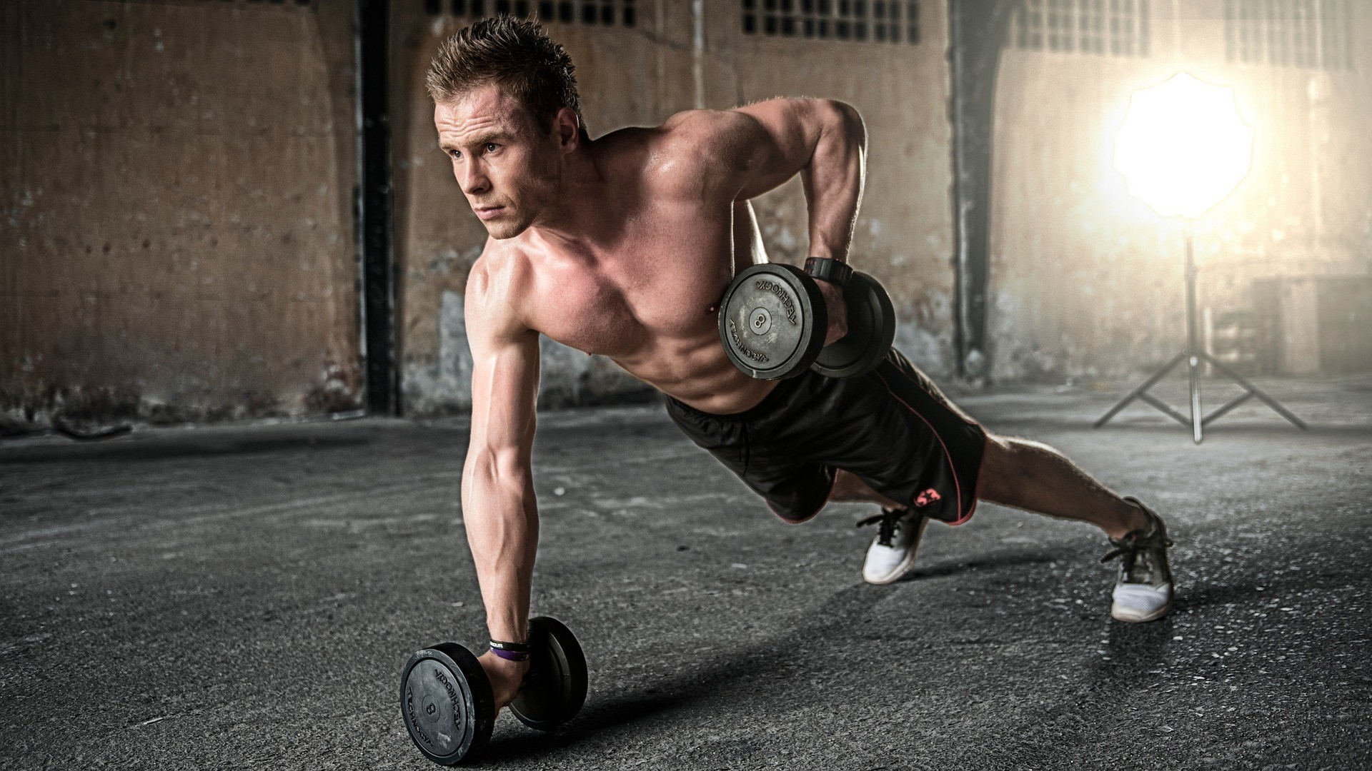 Man doing push-ups on dumbbells, training his core stability in the process