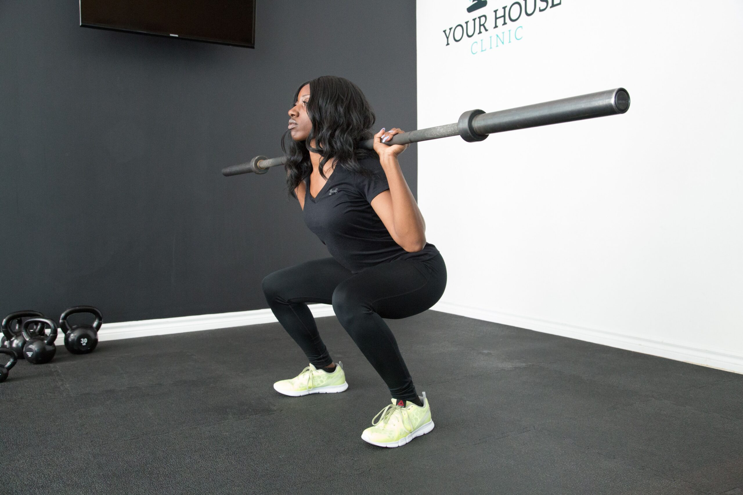 Woman doing a squat with an empty barbell on her back