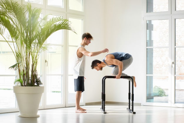 Image of a man doing tuck planche push-ups on parallel bars while another man is watching to assess his form