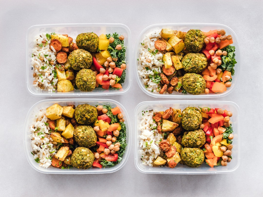 Picture of tupperware containers filled with rice, falafel, veggies and sweet potatoes for a complete nutritious calisthenics meal