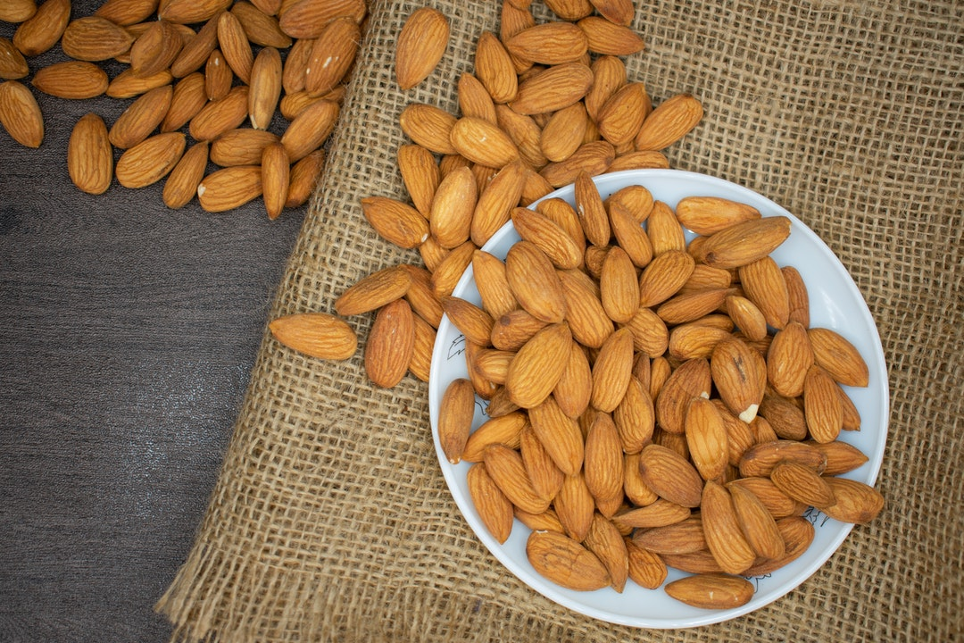 Image of almonds on a plate. Nuts are one of the best sources of fat for a calisthenics diet