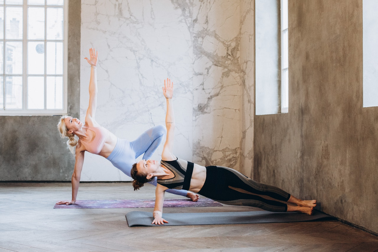 Two girls doing a calisthenics abs workout and doing the side plank