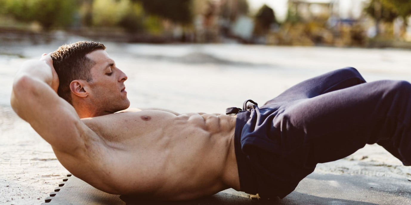 Man on a yoga mat doing crunches on his calisthenics abs workout