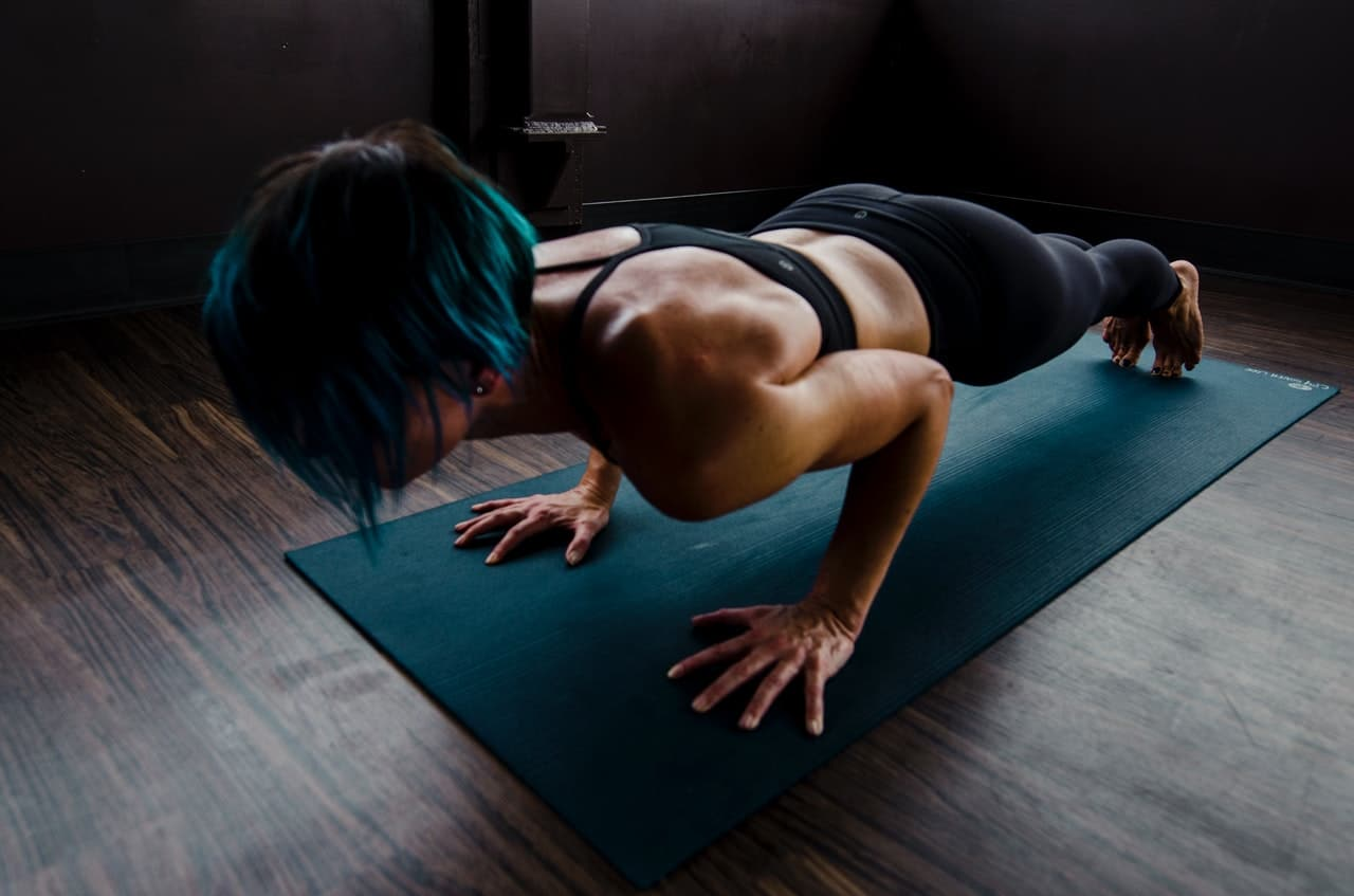 Woman on the bottom position of a push-up on her yoga mat during a calisthenics workout for women