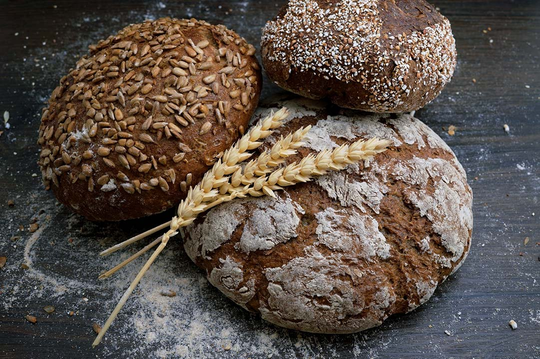 Picture of three loaves of bread and some wheat