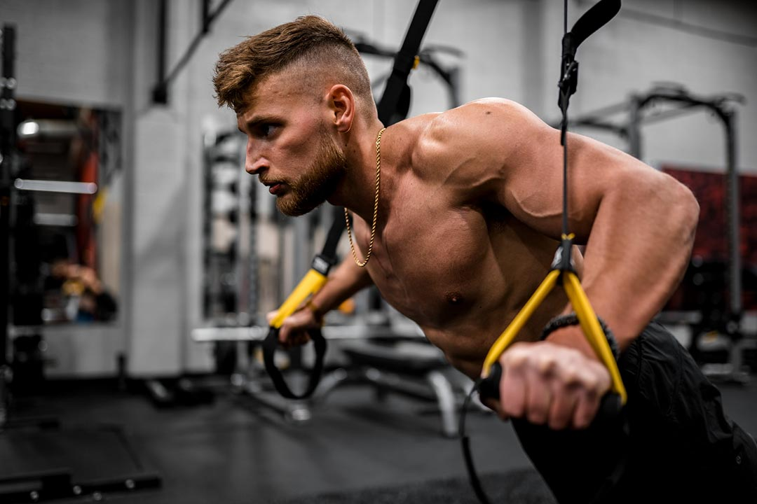 Picture of a man doing chest push-ups on TRX trainer